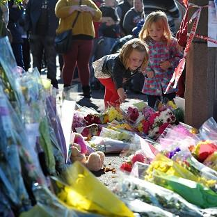 Mourners place flowers outside the fire station in Ely for Karina Menzies who was killed in a hit-and-run on Friday