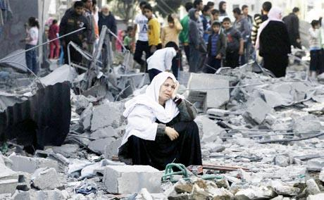 TURMOIL Above, a Palestinian woman sits among rubble following an Israeli air strike on the Rafah refugee camp in southern Gaza.