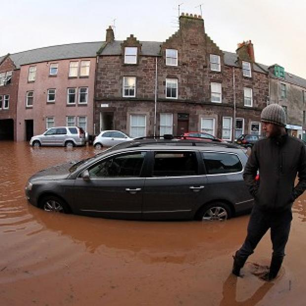 Lancaster And Morecambe Citizen: A man views his flooded car on the high street in Stonehaven, near Aberdeen
