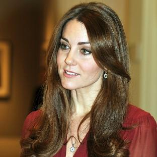 Pictures have been published of the Duchess of Cambridge strolling along a beach in her bikini while on a private holiday