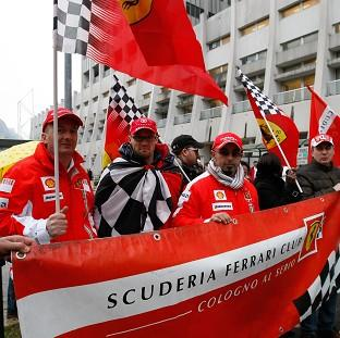 Lancaster And Morecambe Citizen: Supporters of Michael Schumacher hold Ferrari flags to mark his 45th birthday in front of the Grenoble hospital where he is being treated. (AP)