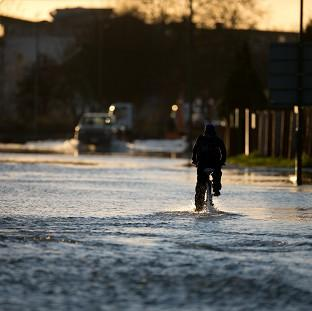 Lancaster And Morecambe Citizen: A man cycles down a flooded road in Chertsey, Surrey