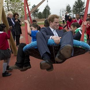Lancaster And Morecambe Citizen: Mayor of London Boris Johnson watches Prince Harry on a swing with local school children at the new Queen Elizabeth Olympic Park in Stratford, east London
