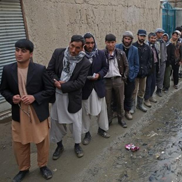 Lancaster And Morecambe Citizen: Afghan men line up for the registration process before they cast their votes at a polling station in Kabul (AP)
