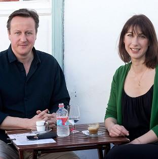 Lancaster And Morecambe Citizen: Prime Minister David Cameron and his wife Samantha stop for a drink by a beach during their holiday on the Spanish island of Lanzarote in Teguise, Spain