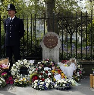 Lancaster And Morecambe Citizen: A police officer stands beside floral tributes during a memorial service held in St James Square, London, to mark the thirtieth anniversary of the death of WPC Yvonne Fletcher