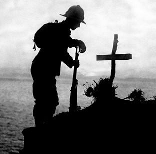 Lancaster And Morecambe Citizen: A soldier pays his respects at the grave of a colleague near Cape Helles, where the Gallipoli landings took place