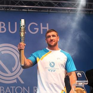 Lancaster And Morecambe Citizen: Alex Arthur carried the Glasgow 2014 Queen's Baton on to the stage as it ended the day in Edinburgh (David Cheskin for Glasgow 2014)