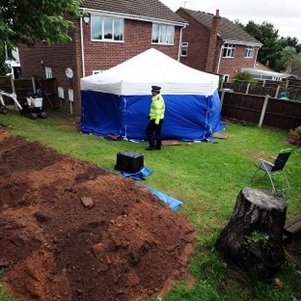 Lancaster And Morecambe Citizen: Police in the garden of a house in Mansfield, where the remains of William and Patricia Wycherley were discovered