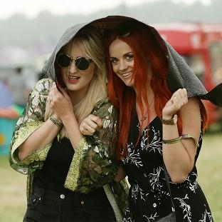 Lancaster And Morecambe Citizen: Festival goers during a rain shower at the Glastonbury Festival, at Worthy Farm in Somerset