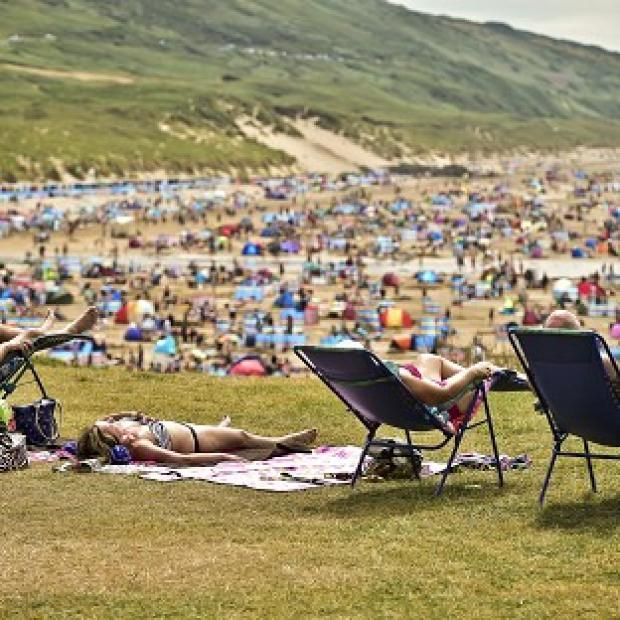 Lancaster And Morecambe Citizen: People relax in sunny weather at Woolacombe, North Devon, as the hot weather continues across the UK