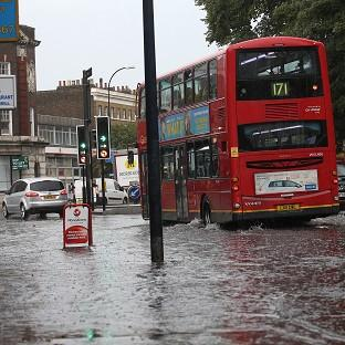 Lancaster And Morecambe Citizen: Traffic drives through a flooded road in New Cross in south east London