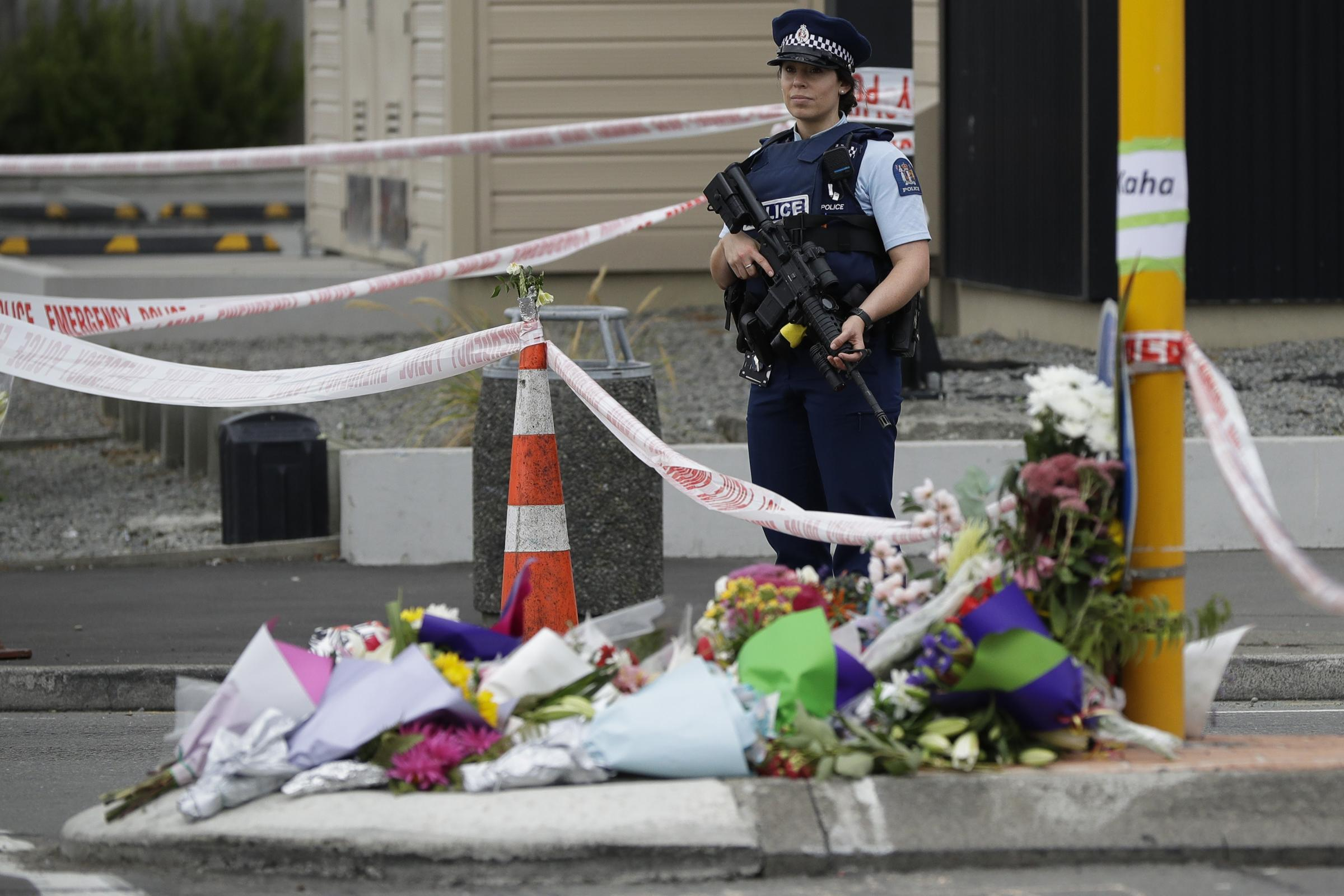 Police stand by a makeshift memorial near the Linwood Mosque in Christchurch